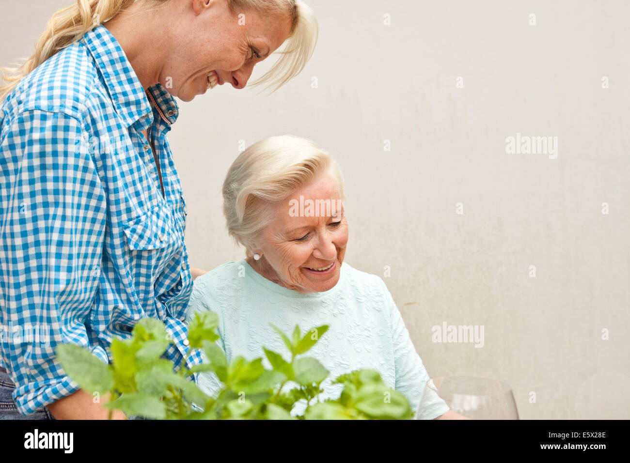 Senior woman and granddaughter chatting at garden table - Stock Image