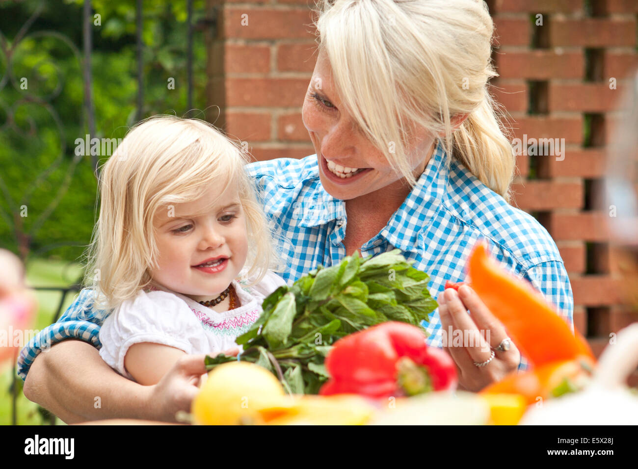 Mother and toddler daughter preparing food at garden table - Stock Image