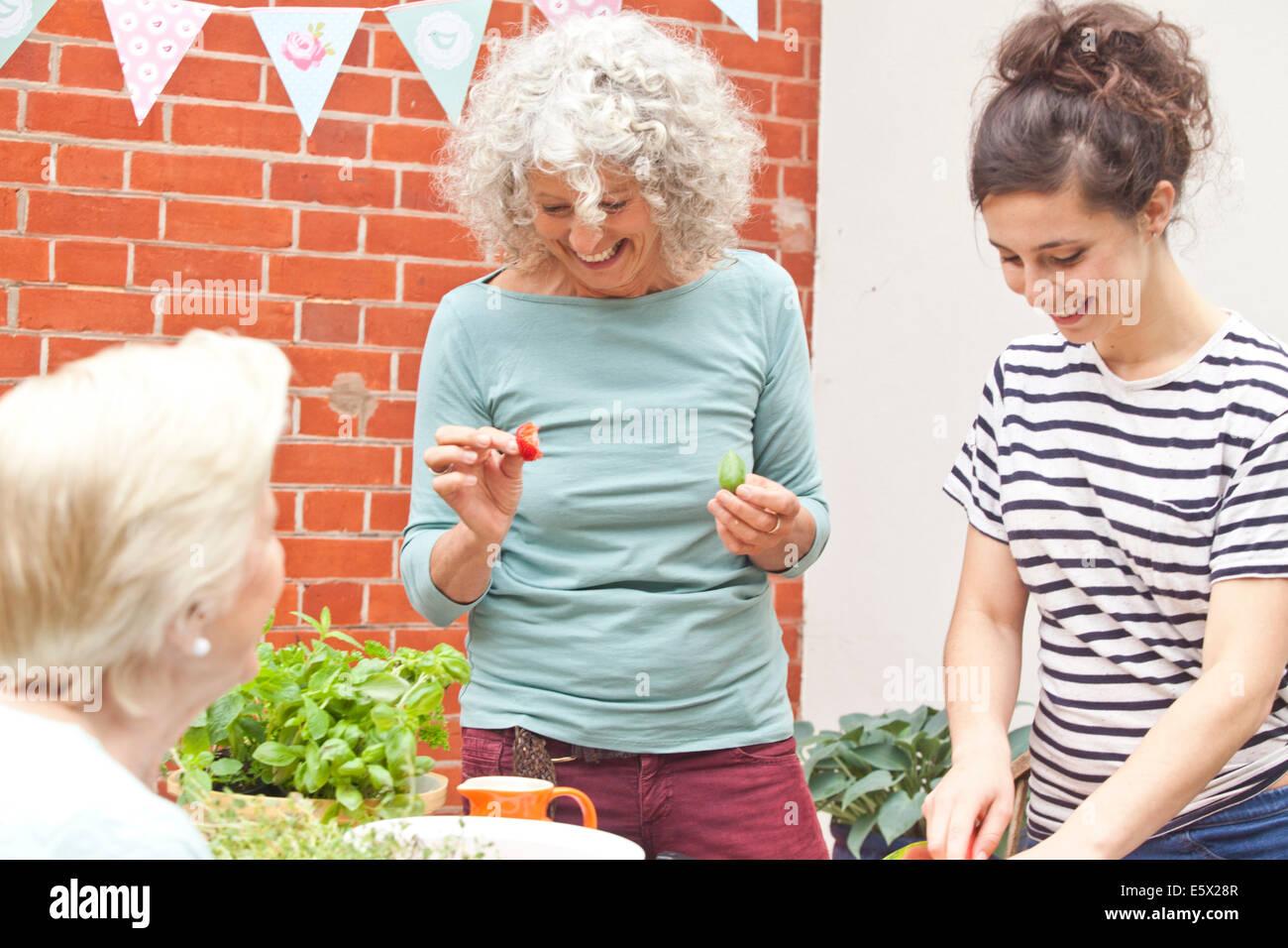 Three women preparing fresh food at garden table - Stock Image