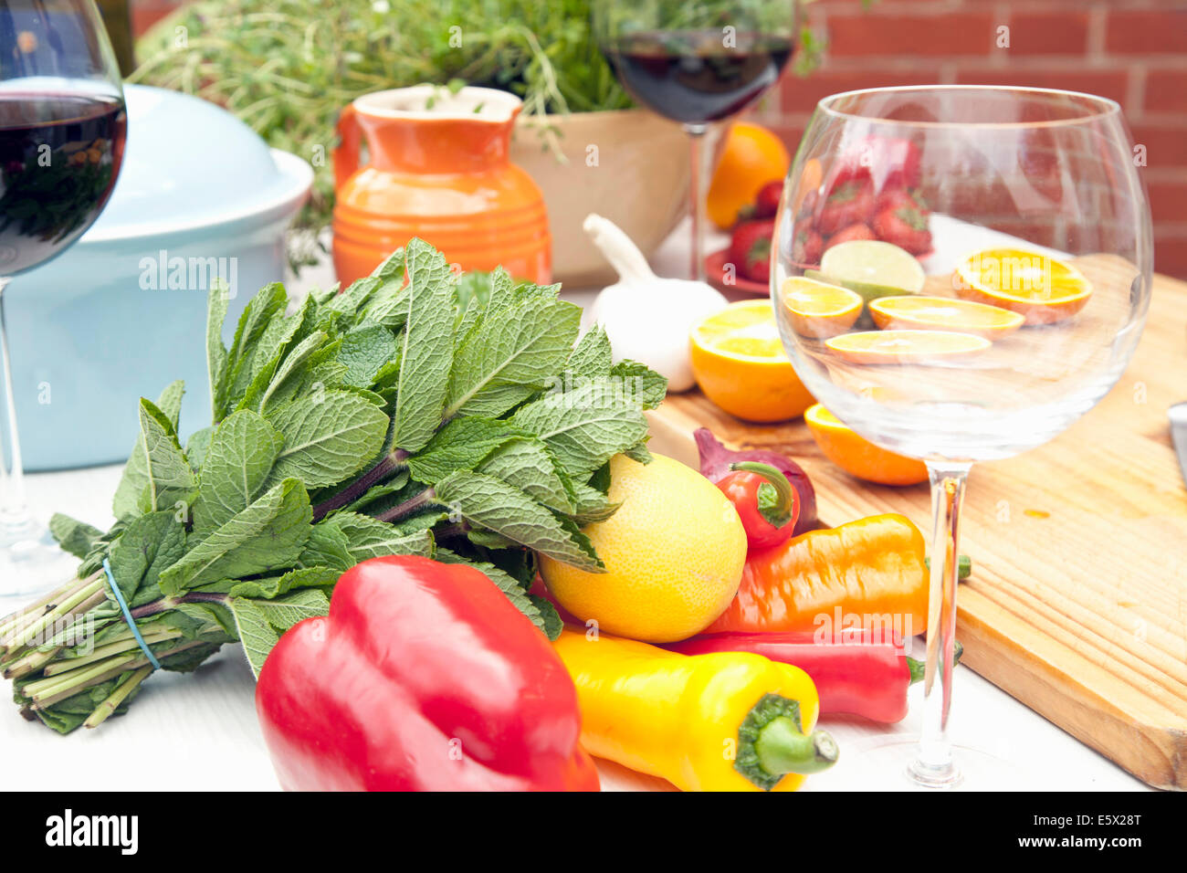 Still life of garden table with herbs, fruit, vegetables and red wine Stock Photo