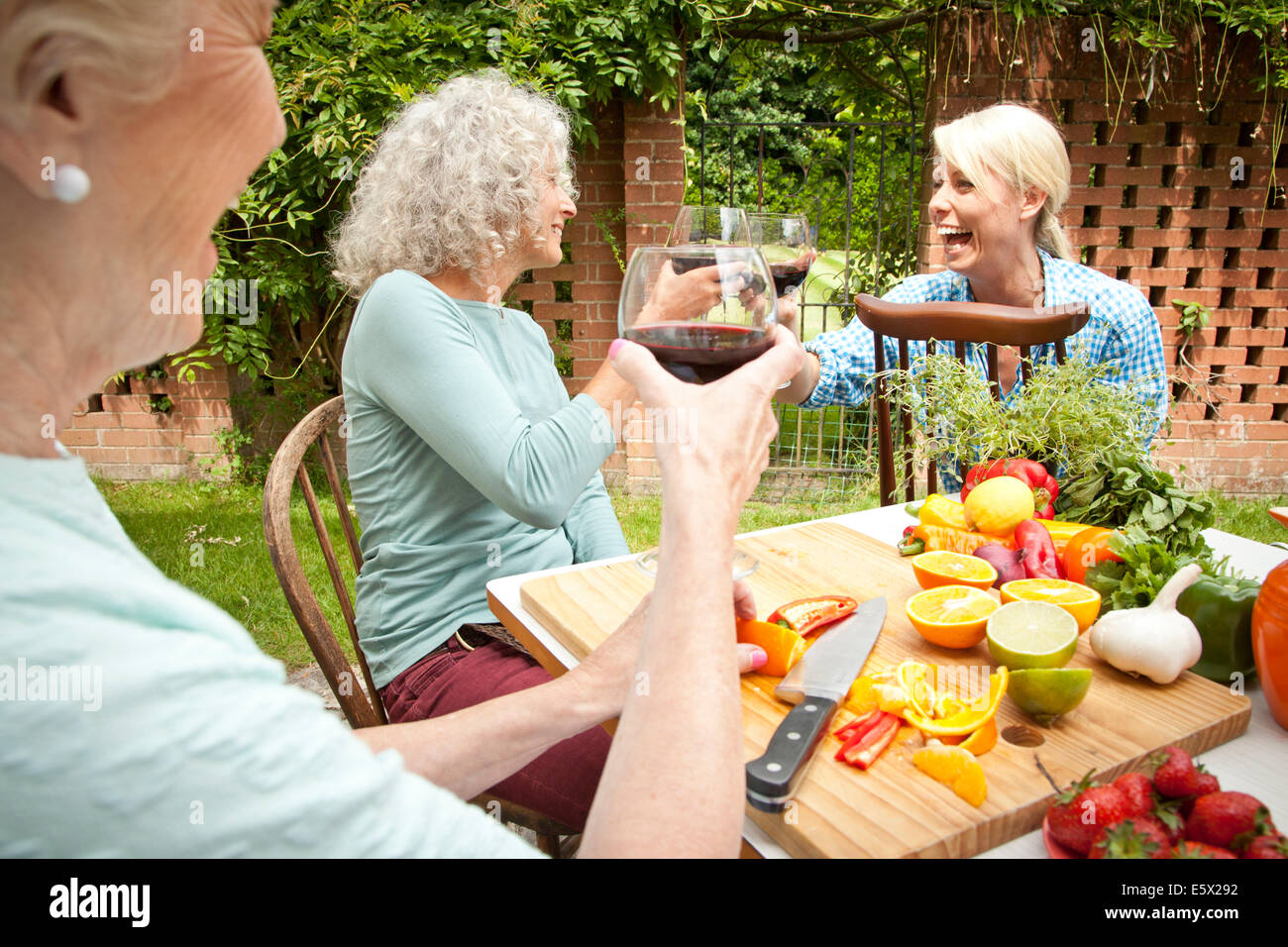 Three generation women raising a glass of red wine while preparing food at garden table - Stock Image