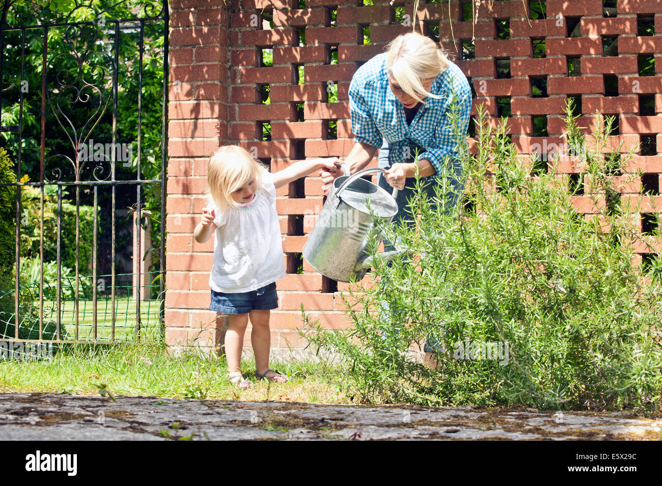 Female toddler helping mother with watering can in garden Stock Photo