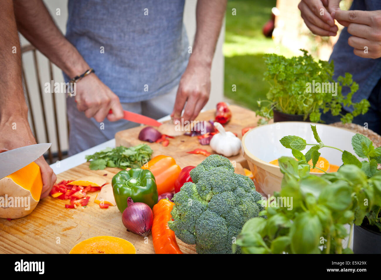 Cropped shot of three male friends preparing food for garden barbecue - Stock Image