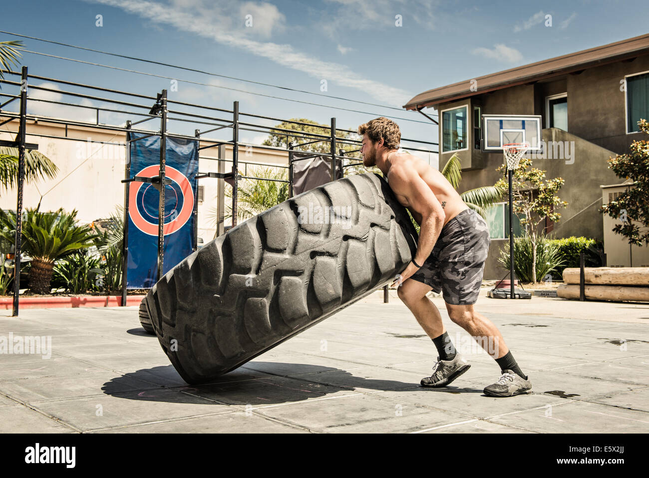 Man lifting huge wheel in basketball court - Stock Image