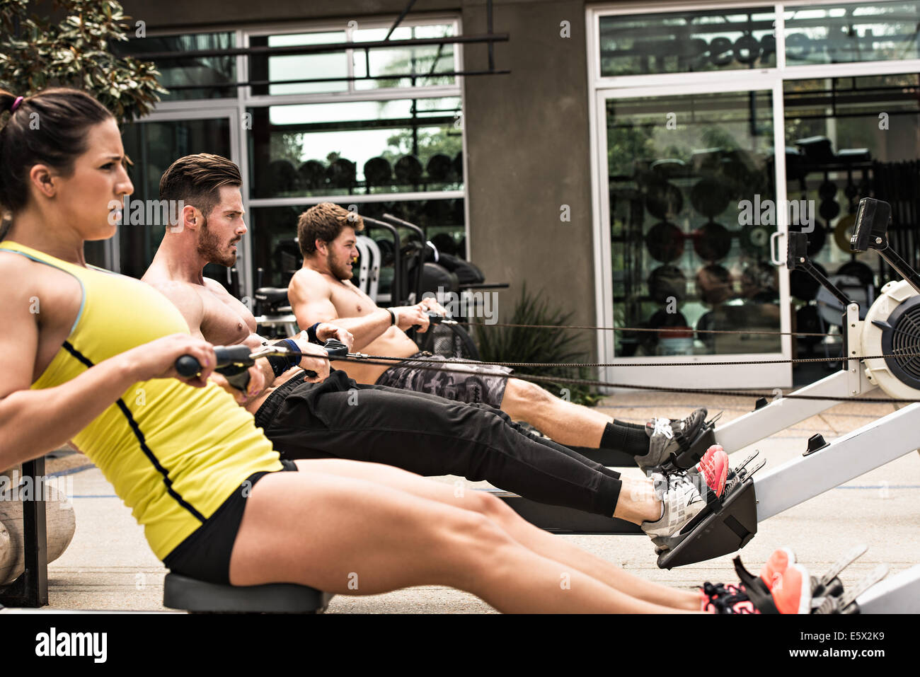 Bodybuilders on rowing machine outdoors - Stock Image