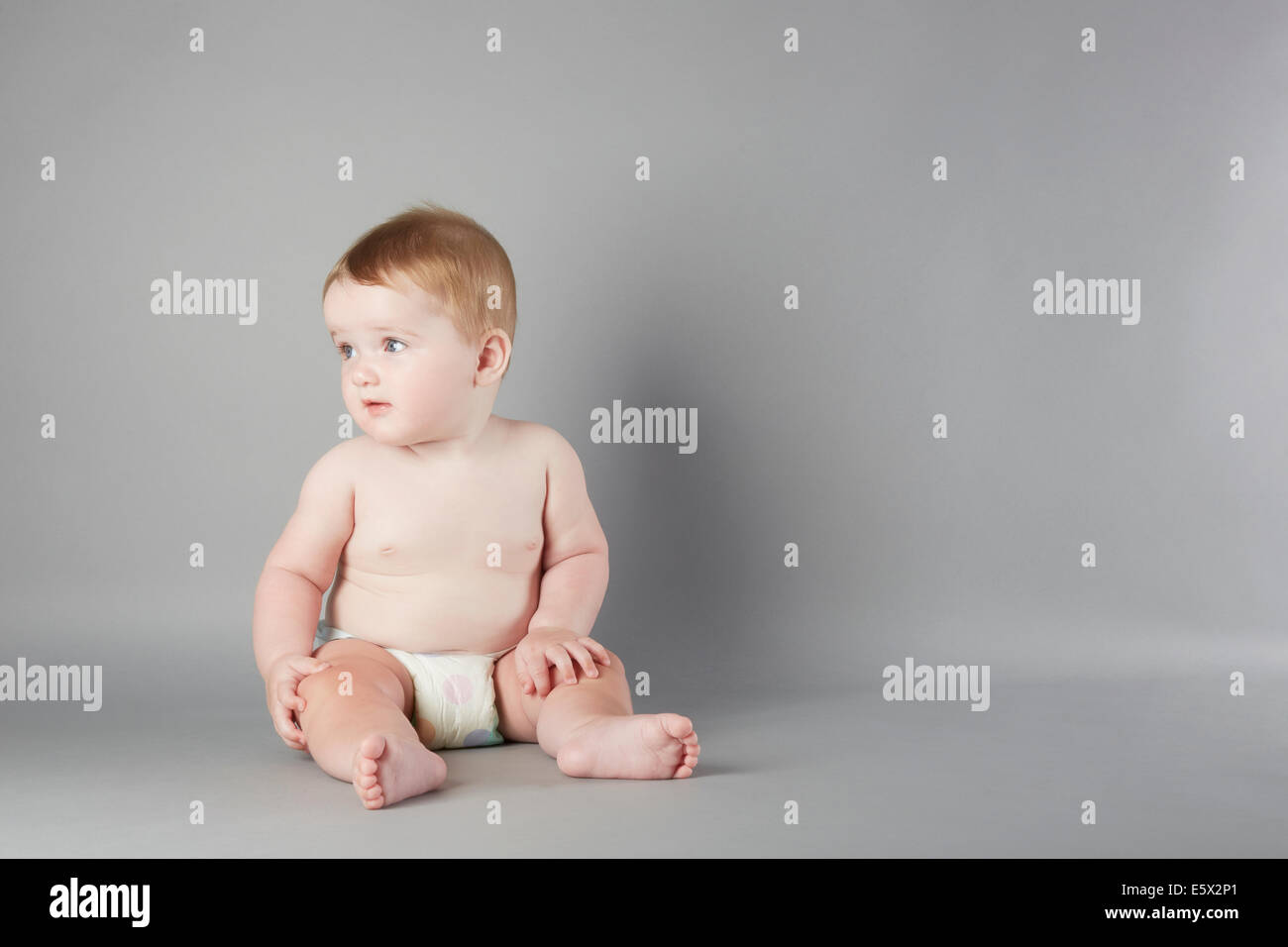 Studio portrait of curious baby girl sitting up - Stock Image