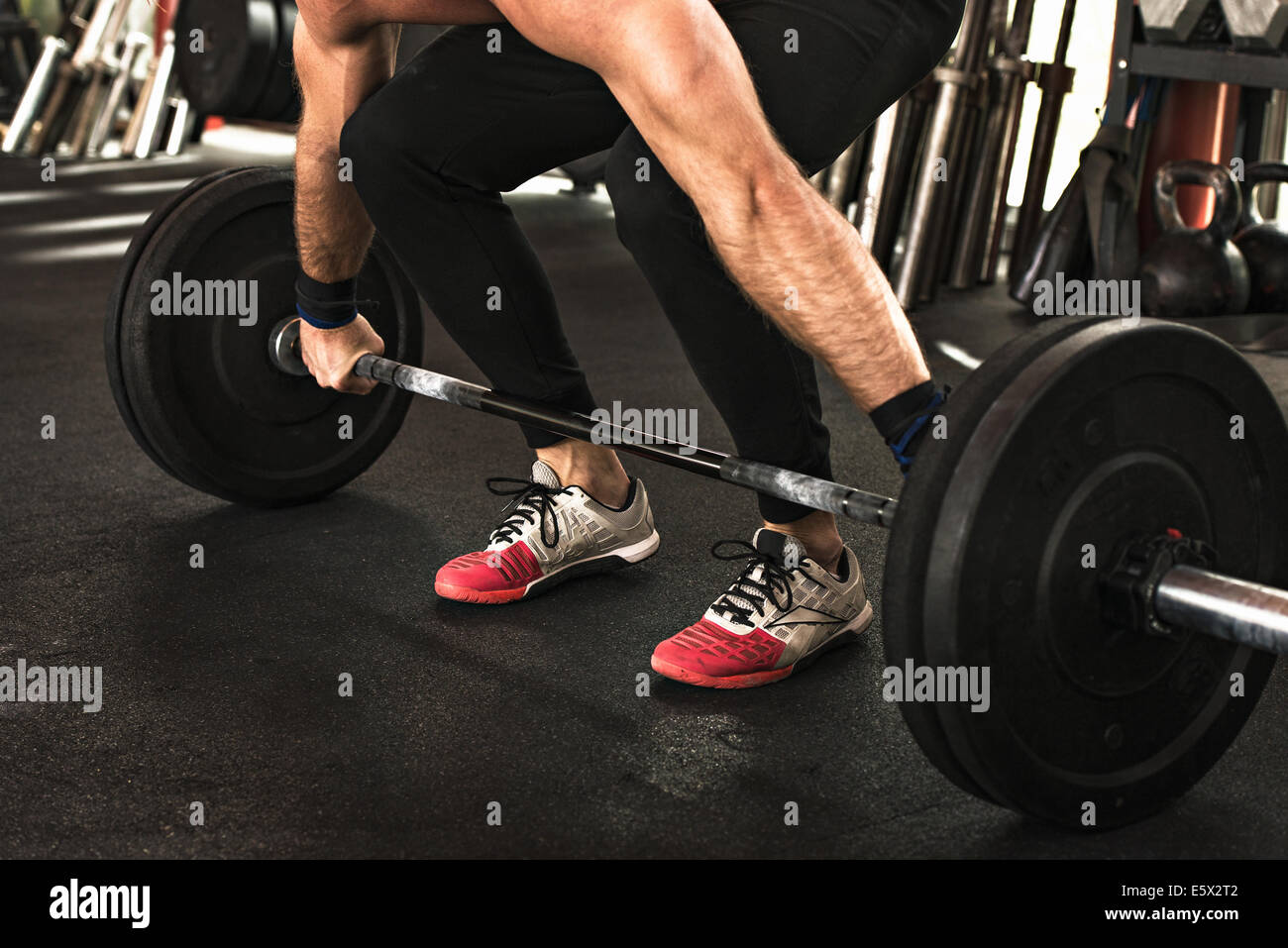 Bodybuilder bending to lift barbell in gym - Stock Image