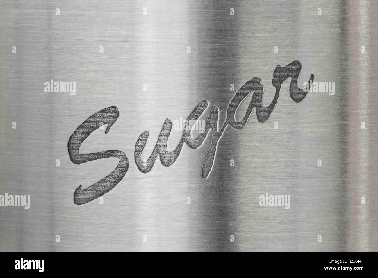 The word sugar on a stainless steel background - Stock Image