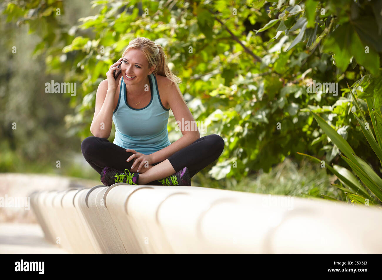 Woman chatting on smartphone on stone seating - Stock Image