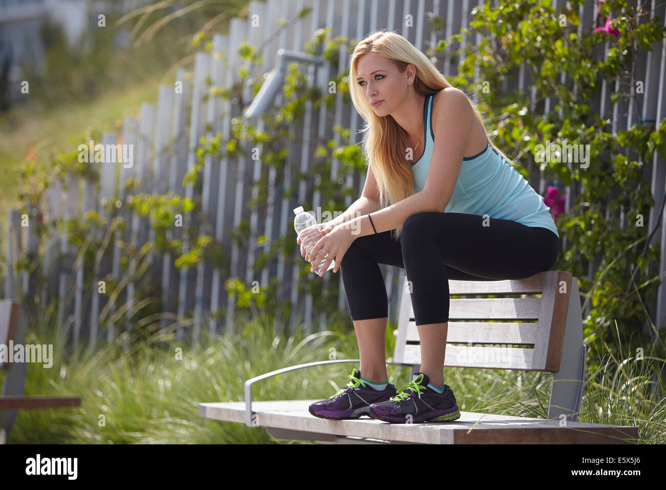 Woman sitting on top of park bench - Stock Image