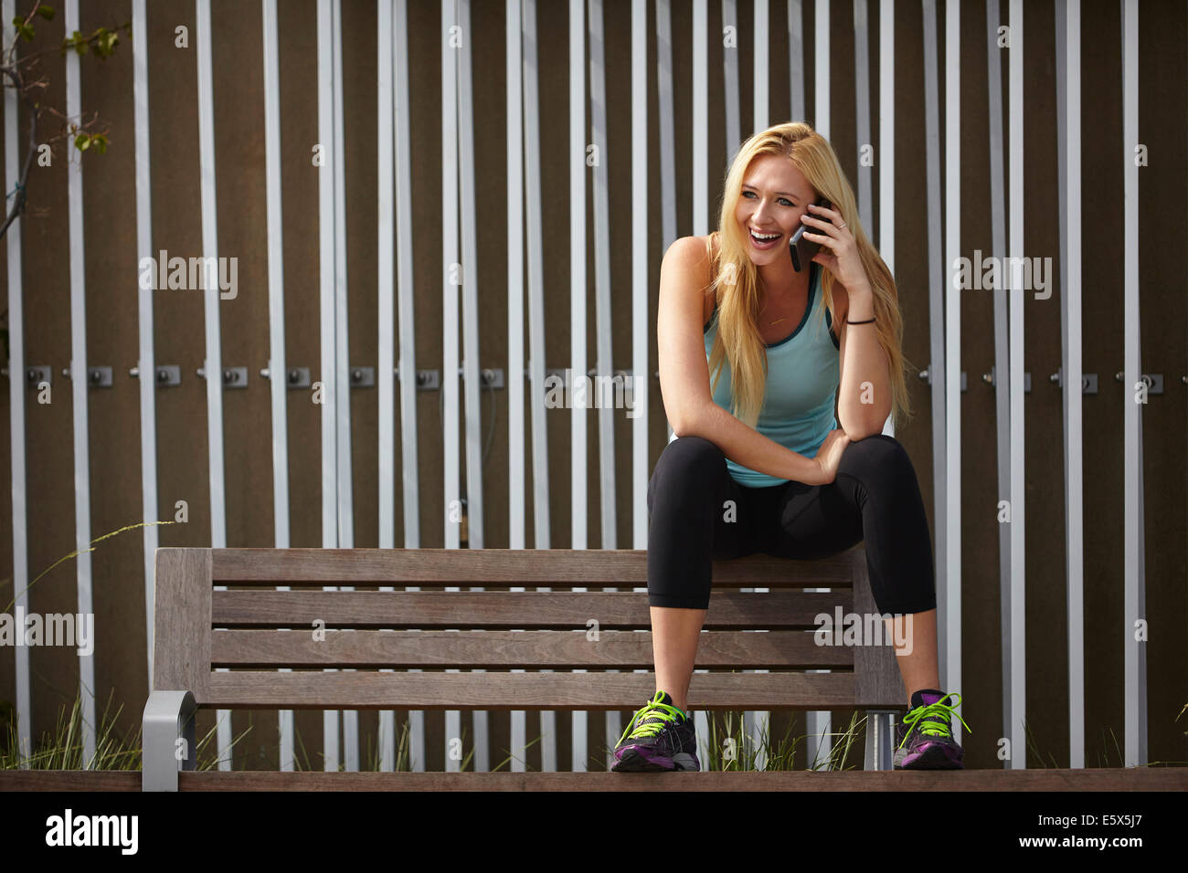 Woman chatting on smartphone on park bench - Stock Image