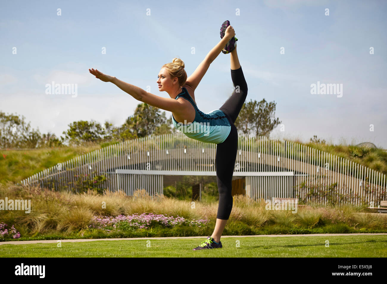 Woman practising yoga in park - Stock Image