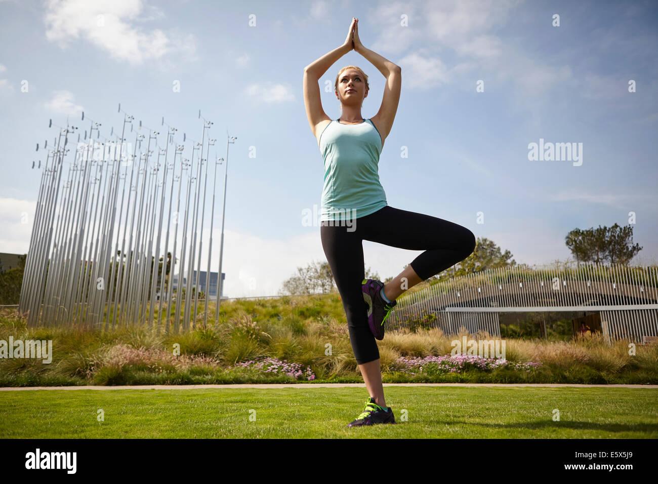 Woman practising yoga in park - Stock Image