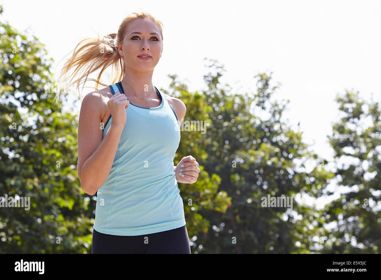 Woman running in park - Stock Image