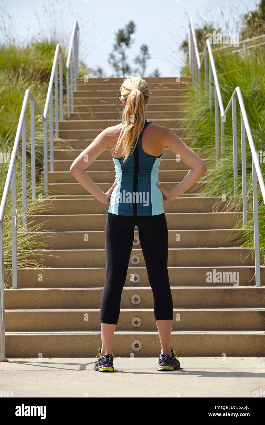 Woman standing at base of stairs - Stock Image