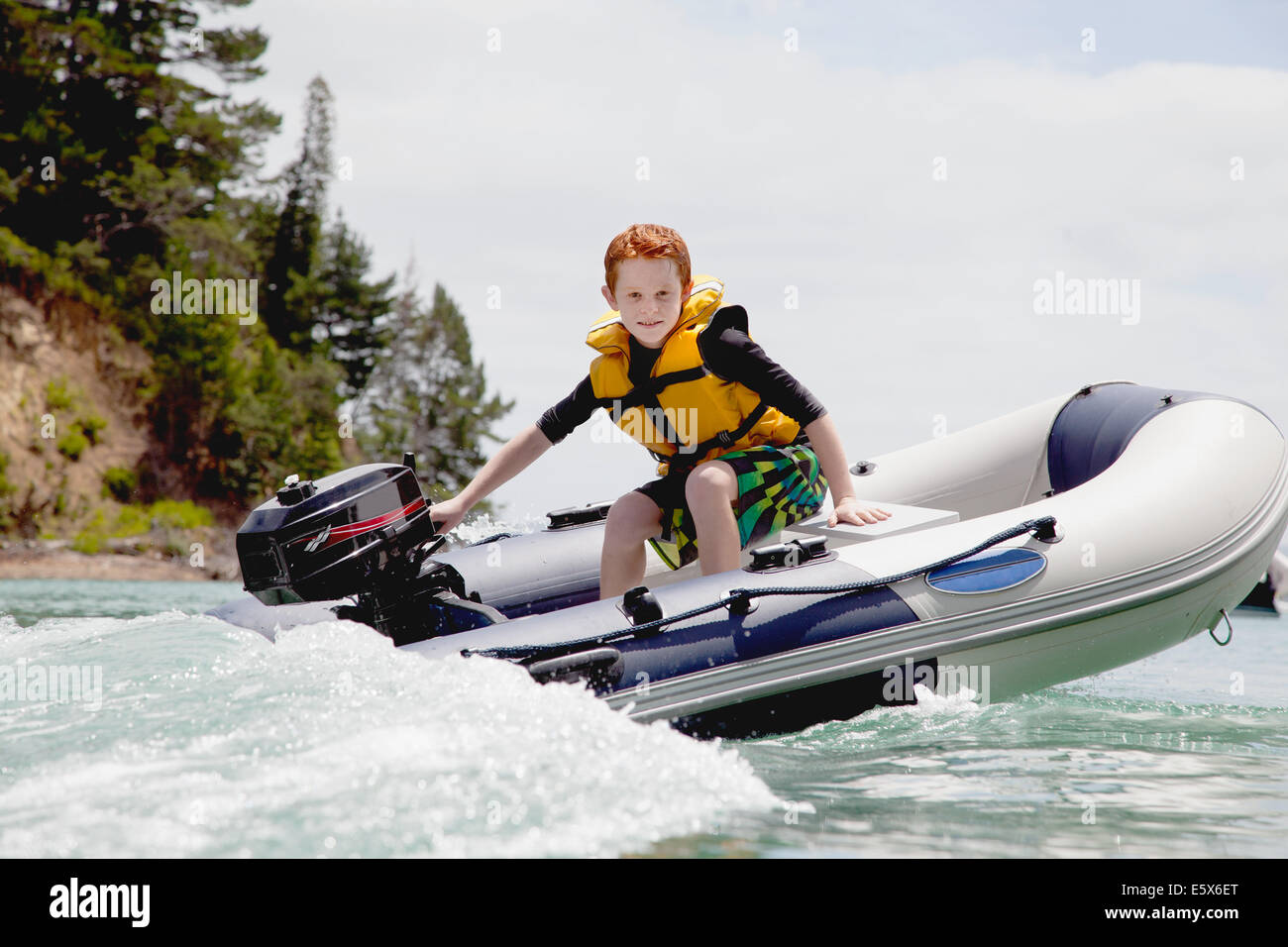Boy steering speeding motor dinghy at sea - Stock Image