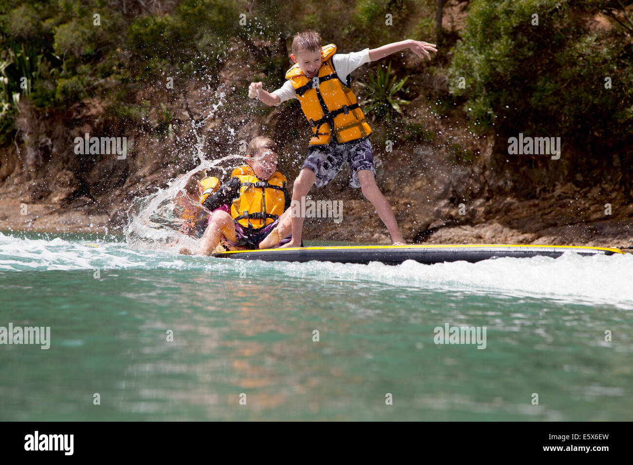 Brothers and sister splashing from paddleboard at sea - Stock Image