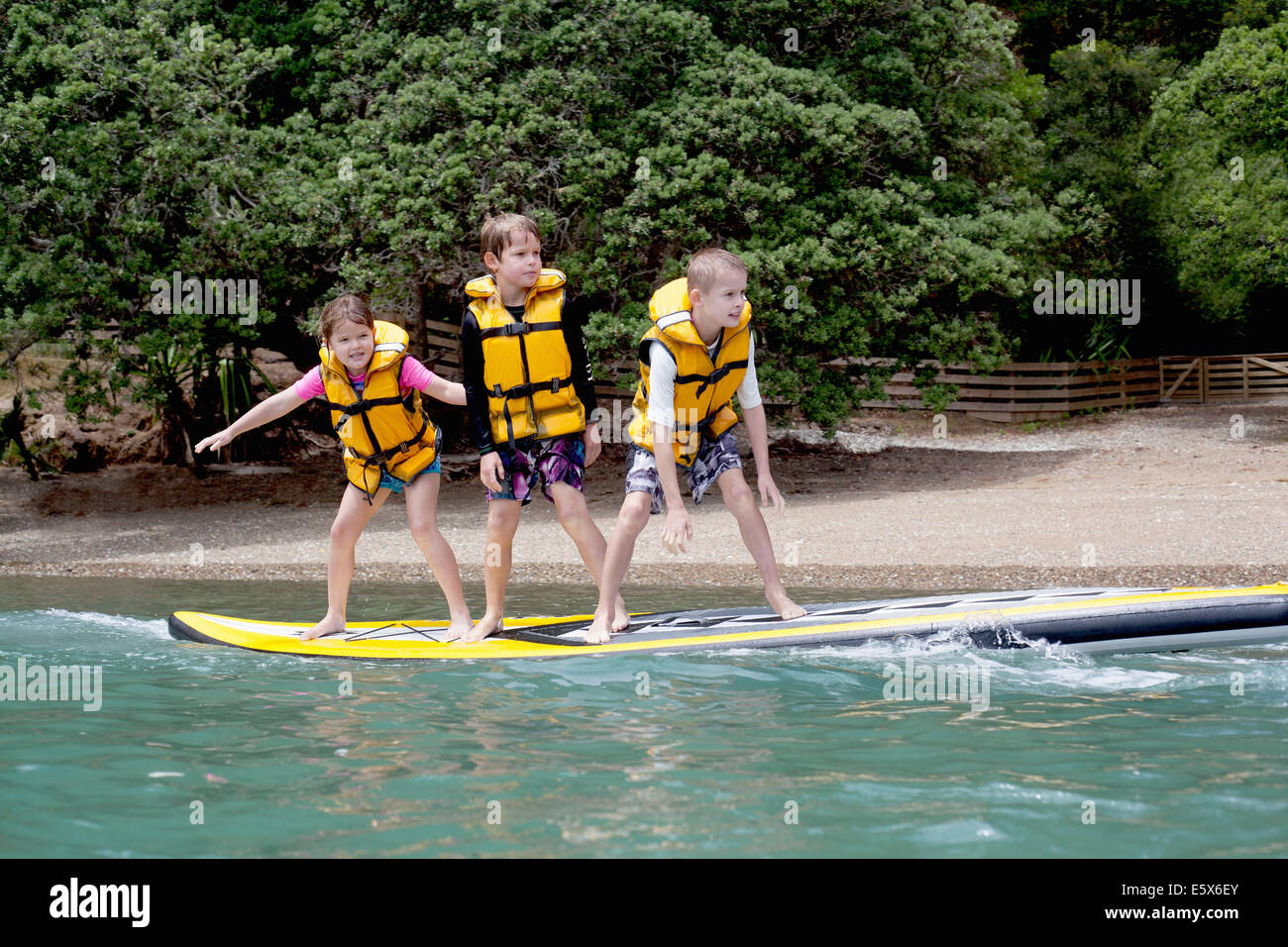 Brothers and sister standing on paddleboard at sea - Stock Image