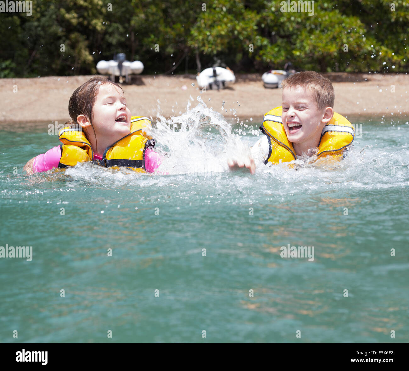 Brother and sister play fighting and splashing in sea - Stock Image