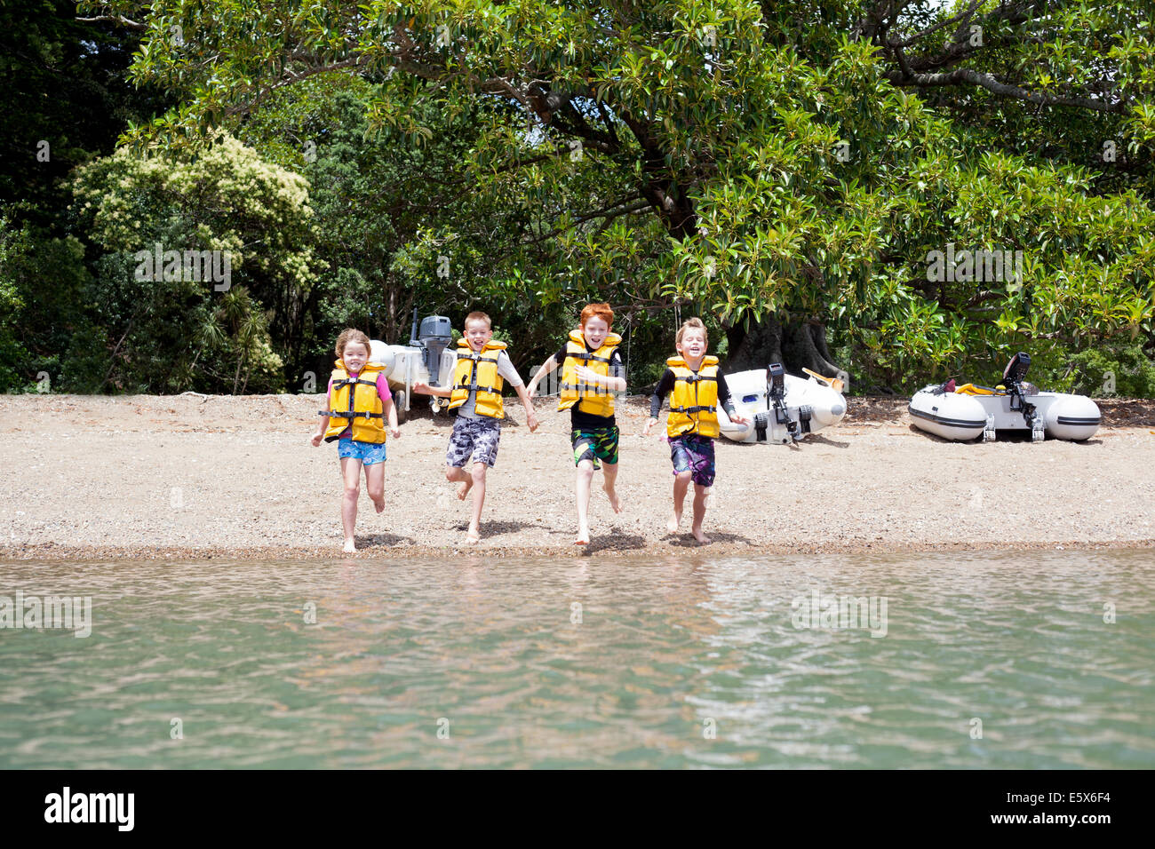 Brothers and sister running hand in hand into sea - Stock Image