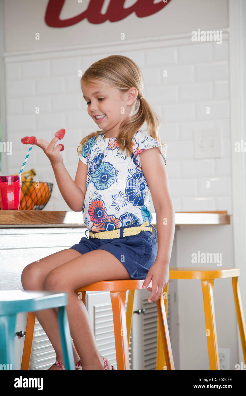 Girl sitting on kitchen stool with raspberries on her fingers - Stock Image