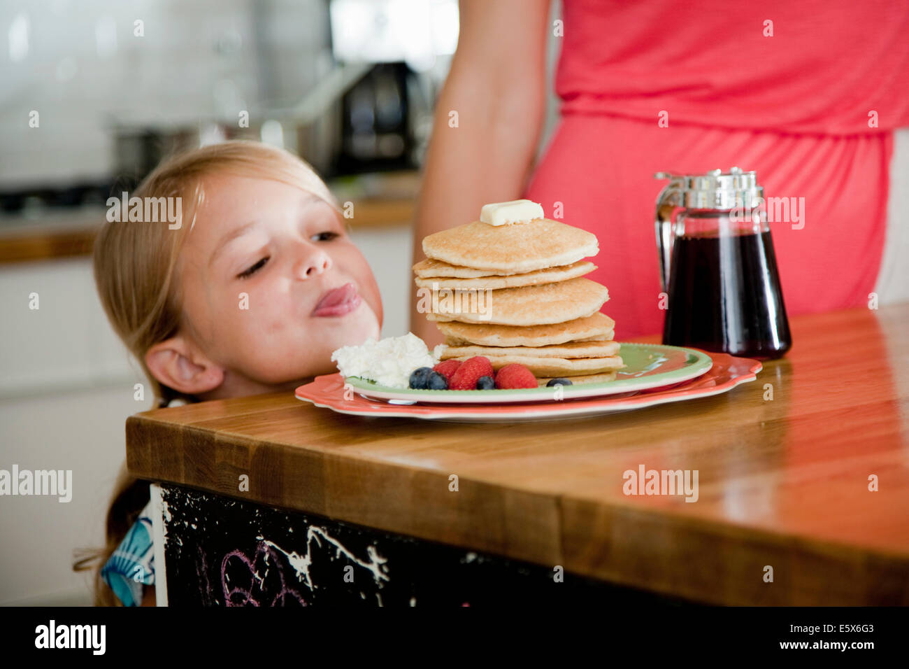 Mischievous girl gazing at pancakes on breakfast bar - Stock Image