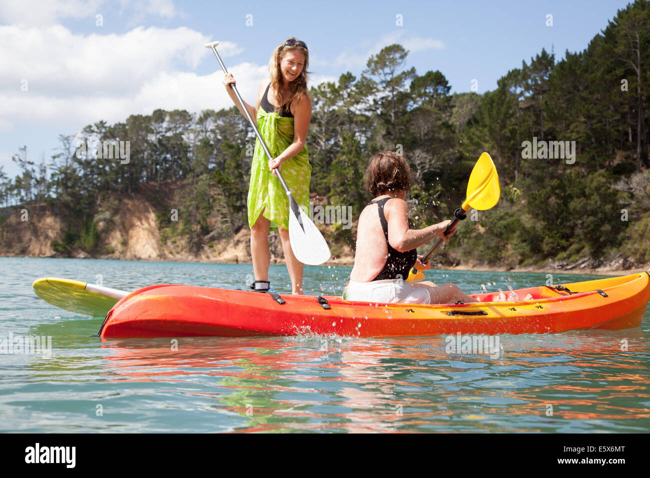 Senior woman and daughter playfighting from kayak and paddleboard - Stock Image