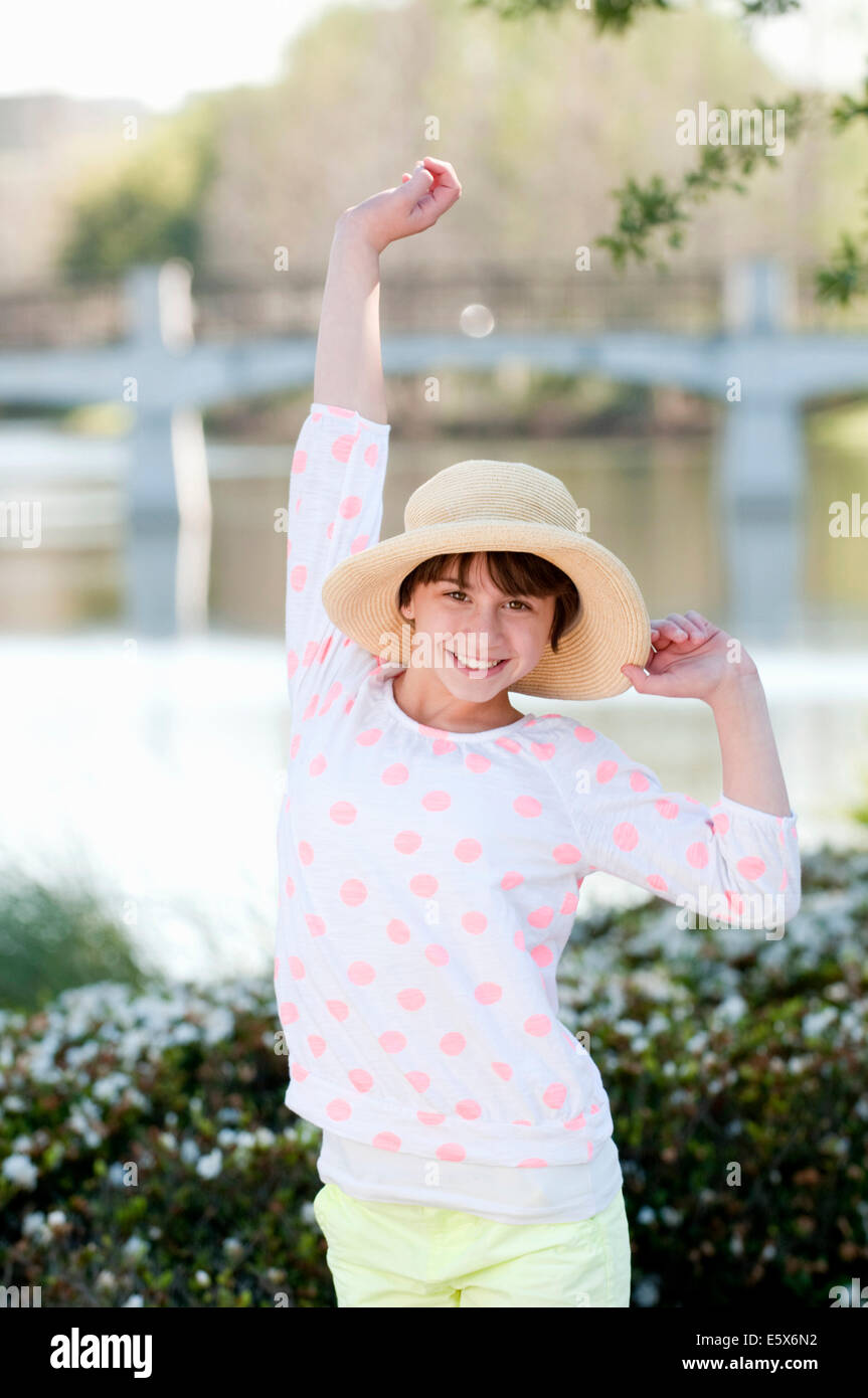 Portrait of ten year old girl with hand raised - Stock Image