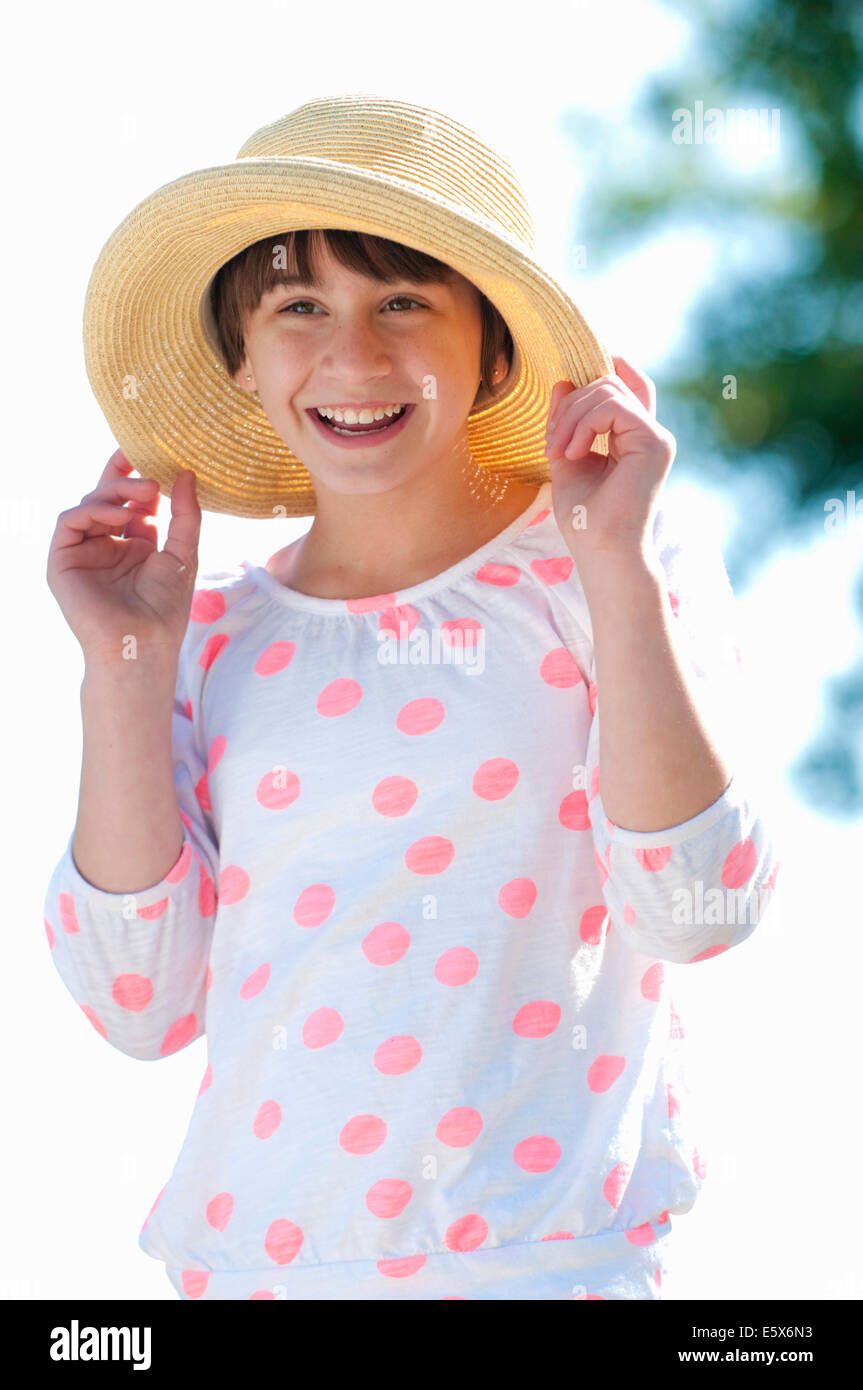 Portrait of ten year old girl holding onto straw hat - Stock Image