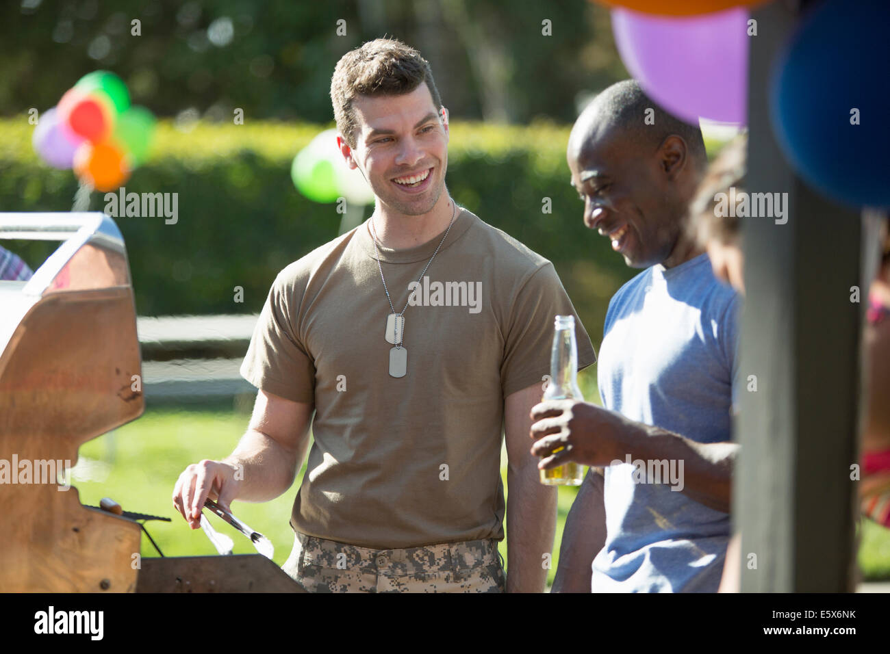 Male soldier barbecuing with friends at homecoming party - Stock Image