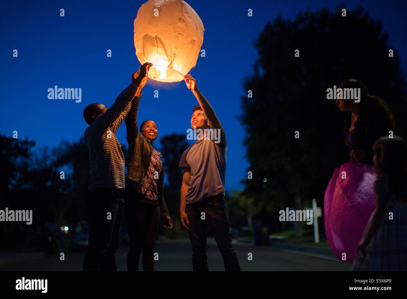 Friends holding up sky lantern to celebrate - Stock Image