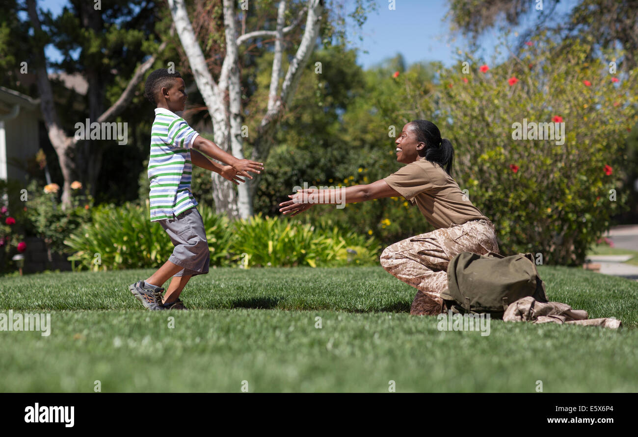 Female soldier reaching out for son in garden on homecoming - Stock Image