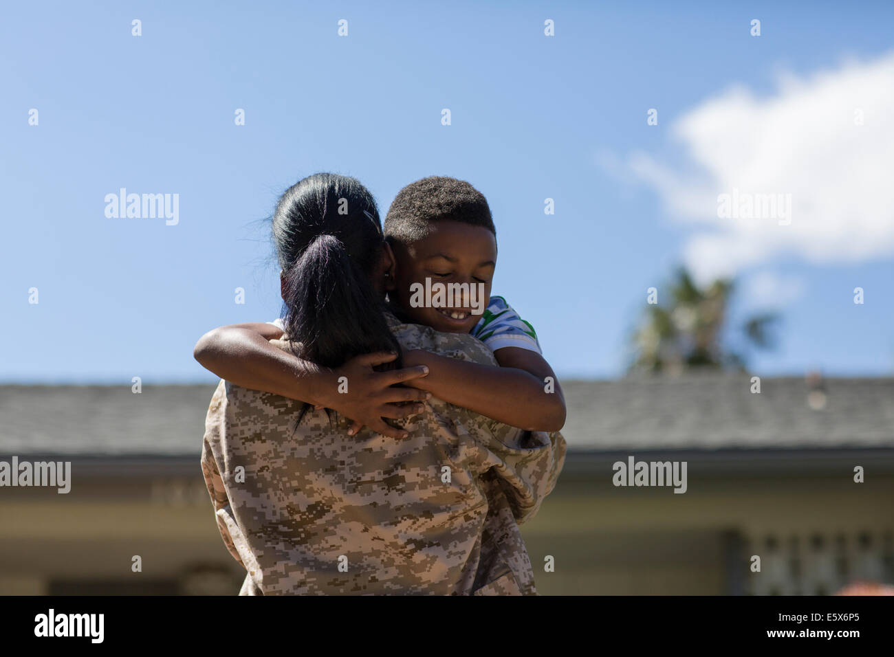 Rear view of female soldier hugging son on homecoming - Stock Image