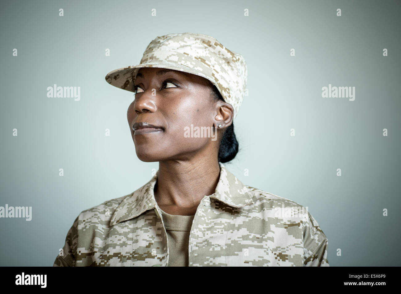 Studio portrait of confident female soldier looking sideways - Stock Image