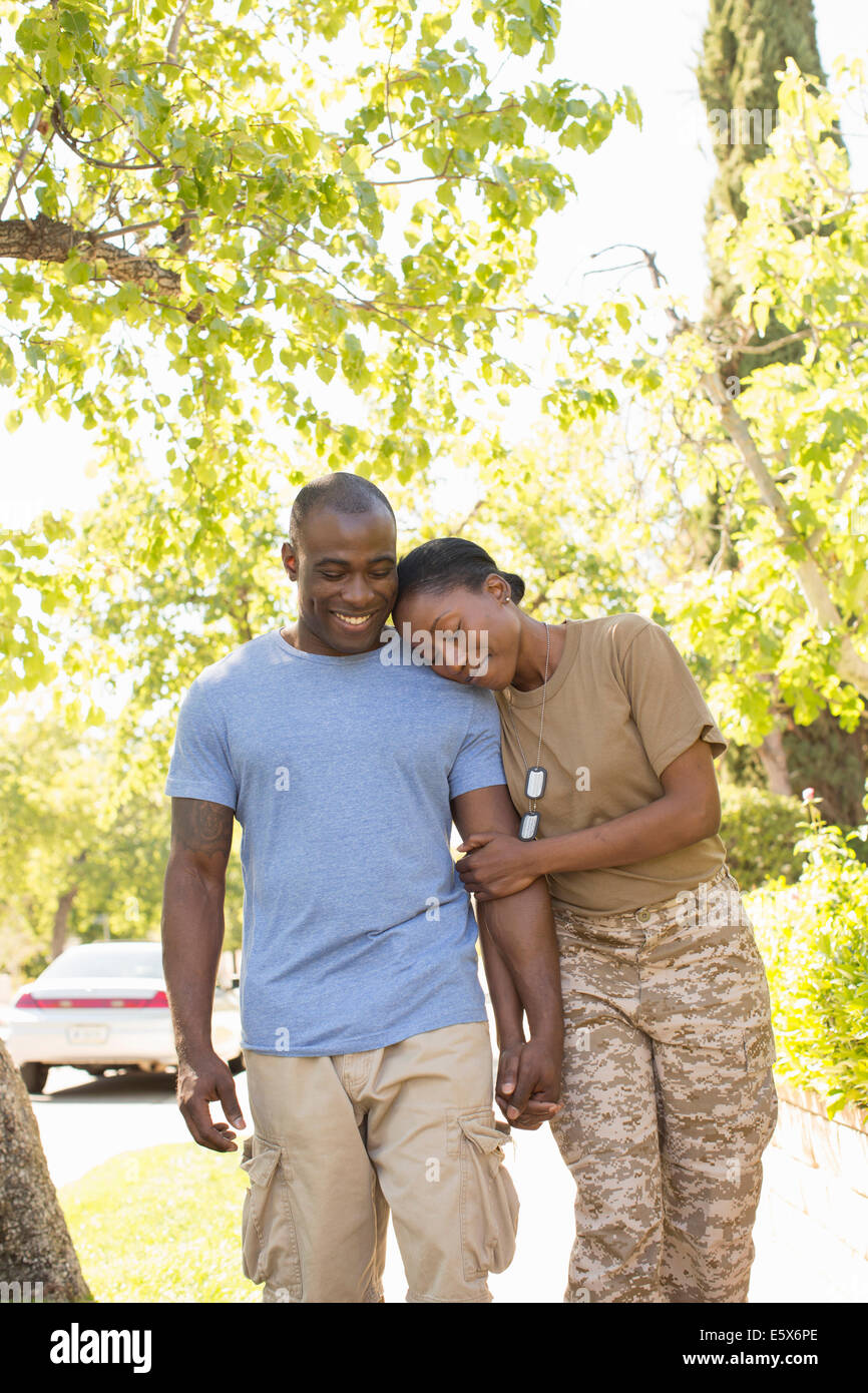Female soldier resting head on husbands shoulder whilst strolling on homecoming - Stock Image