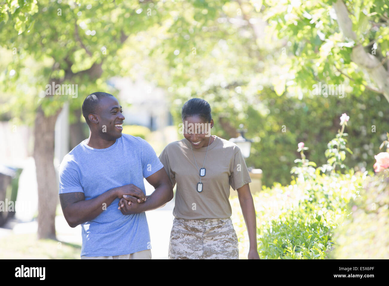 Female soldier holding husband's hand whilst strolling on homecoming - Stock Image