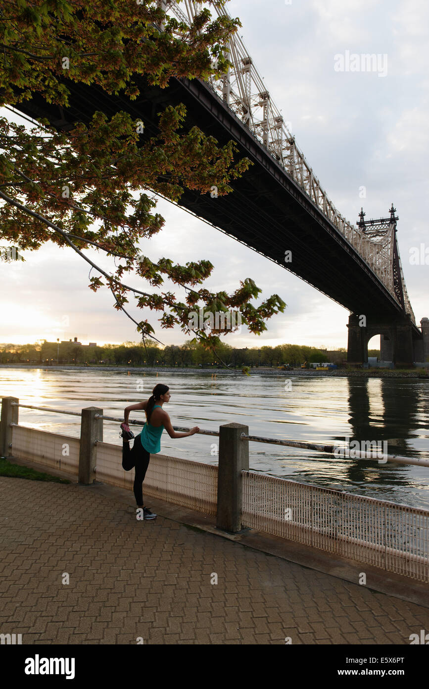Young female runner stretching on waterfront, Roosevelt Island, New York City, USA - Stock Image