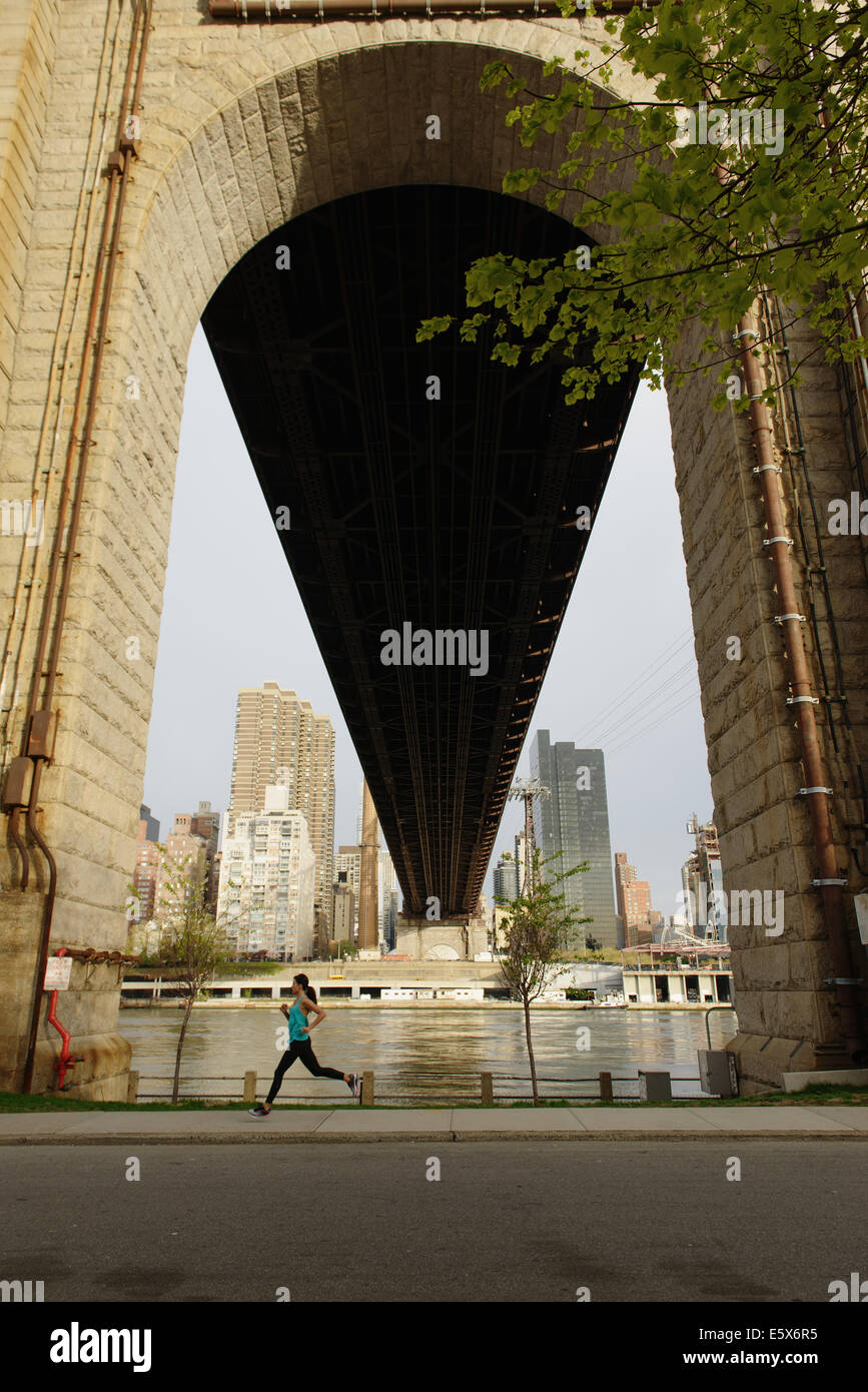 Young woman running next to bridge arch, Roosevelt Island, New York City, USA Stock Photo