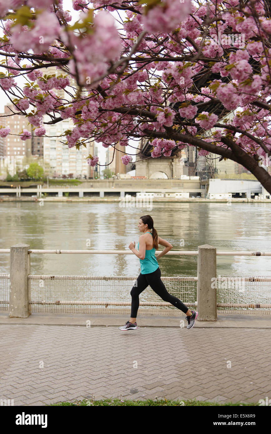 Young female runner running on city waterfront - Stock Image