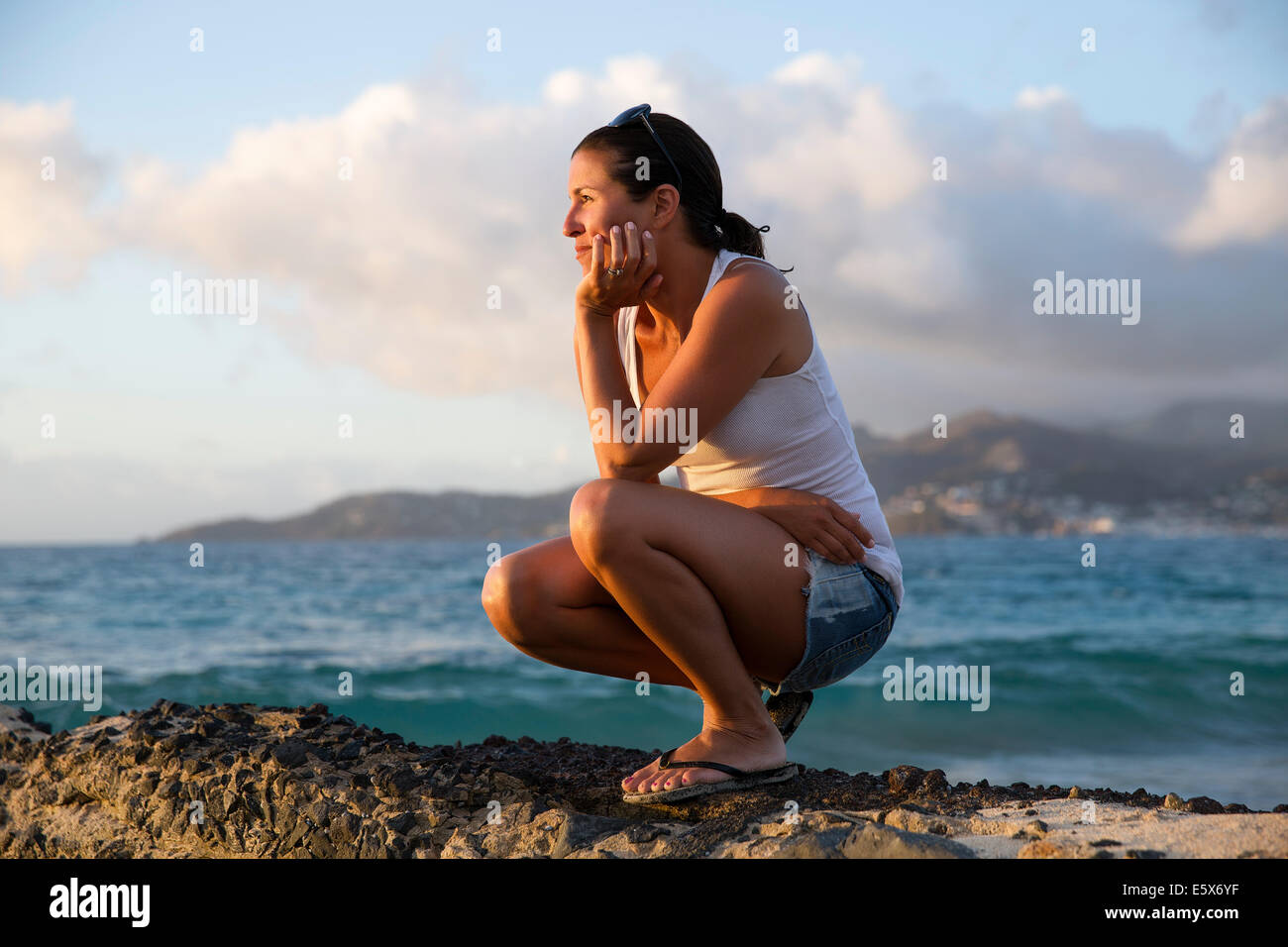 Mid adult woman crouching and gazing at caribbean sea from pier, Spice Island beach resort, Grenada, Stock Photo