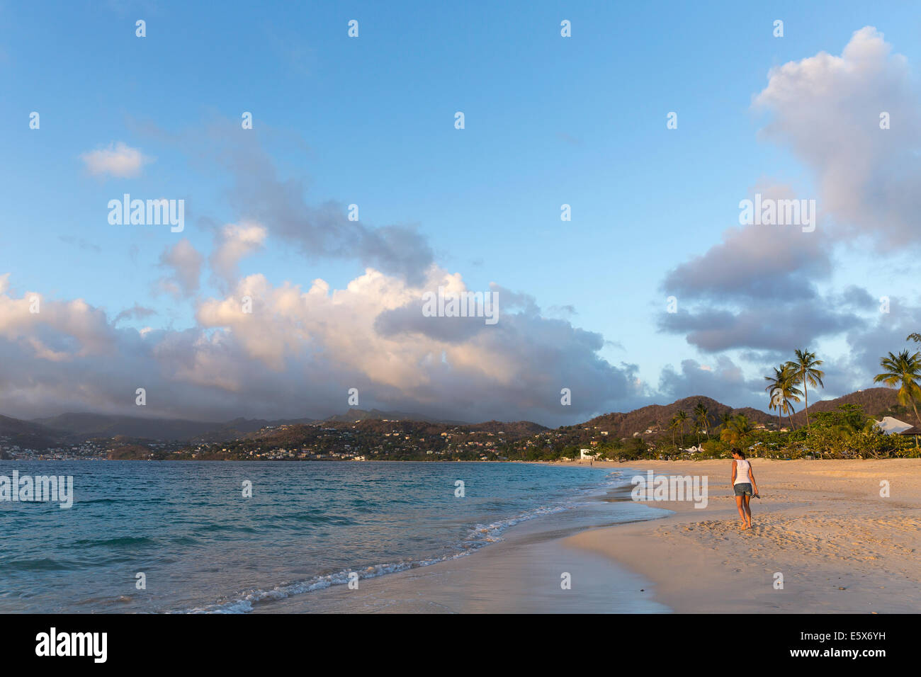Rear view of mid adult woman strolling on beach, Spice Island beach resort, Grenada, Caribbean - Stock Image