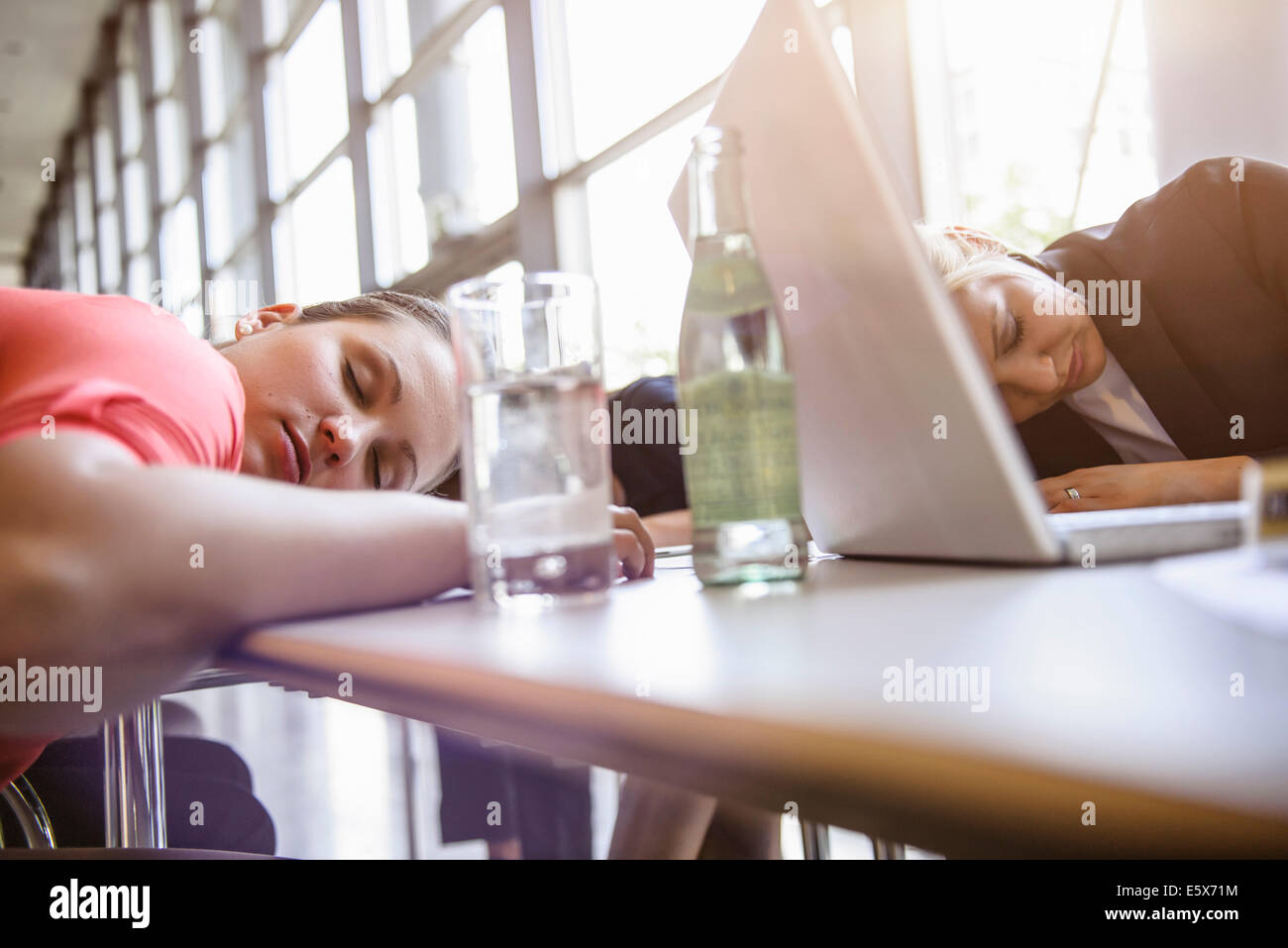 Businesswomen exhausted at brainstorm meeting - Stock Image