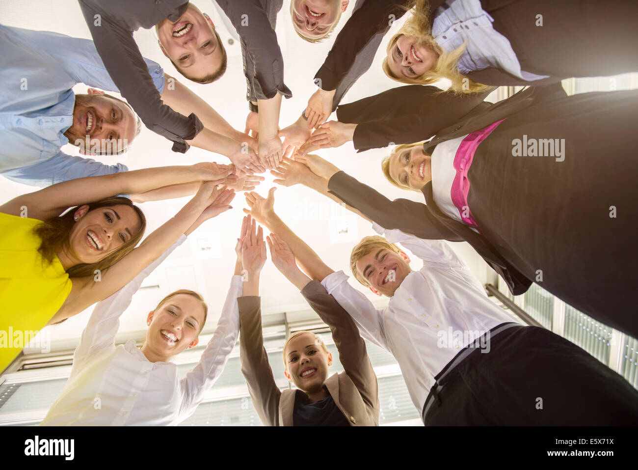 Worms eye view of seven business men and women in a circle holding hands in office - Stock Image