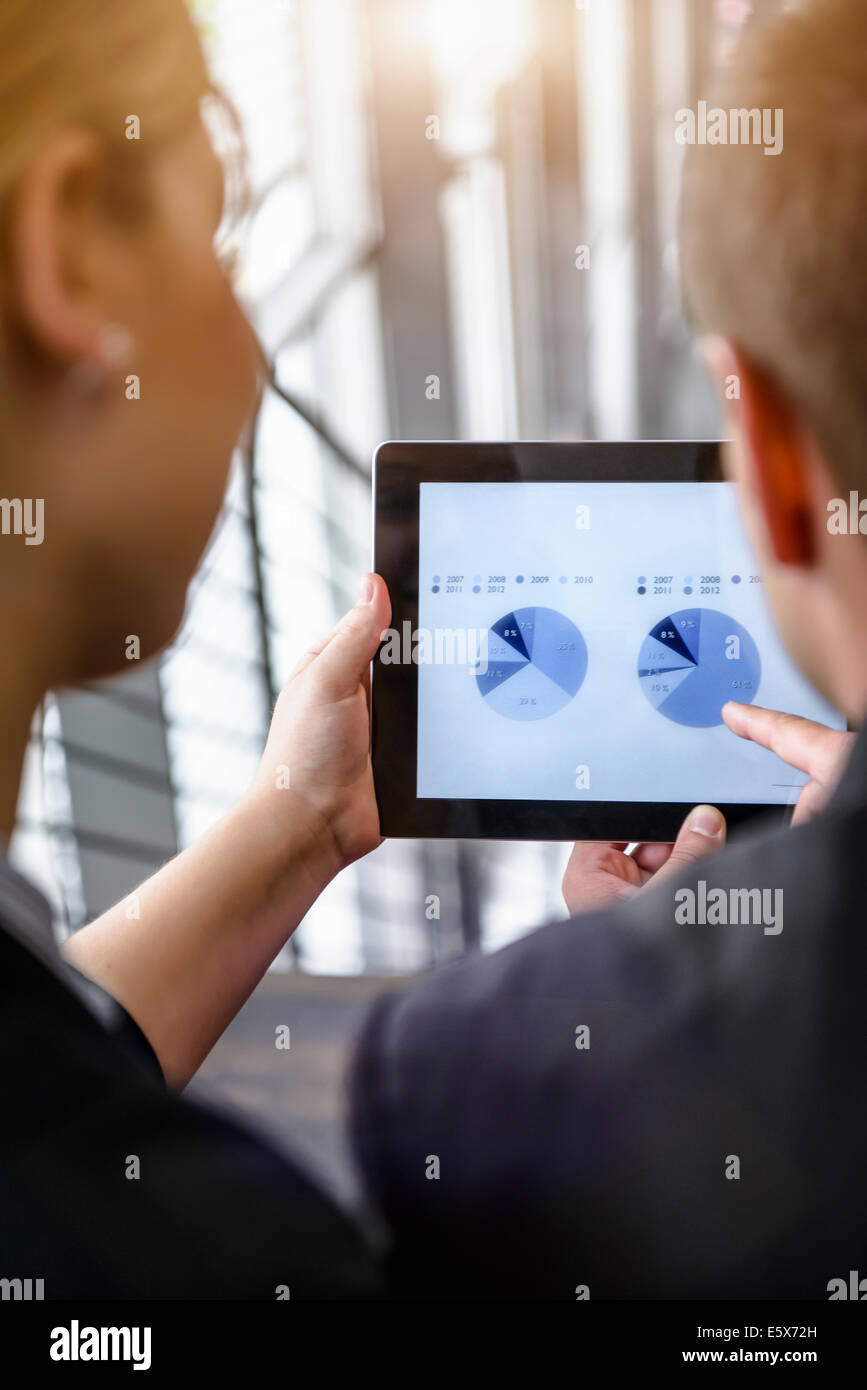 Over shoulder view of businesswoman and man using touchscreen on digital tablet in office - Stock Image