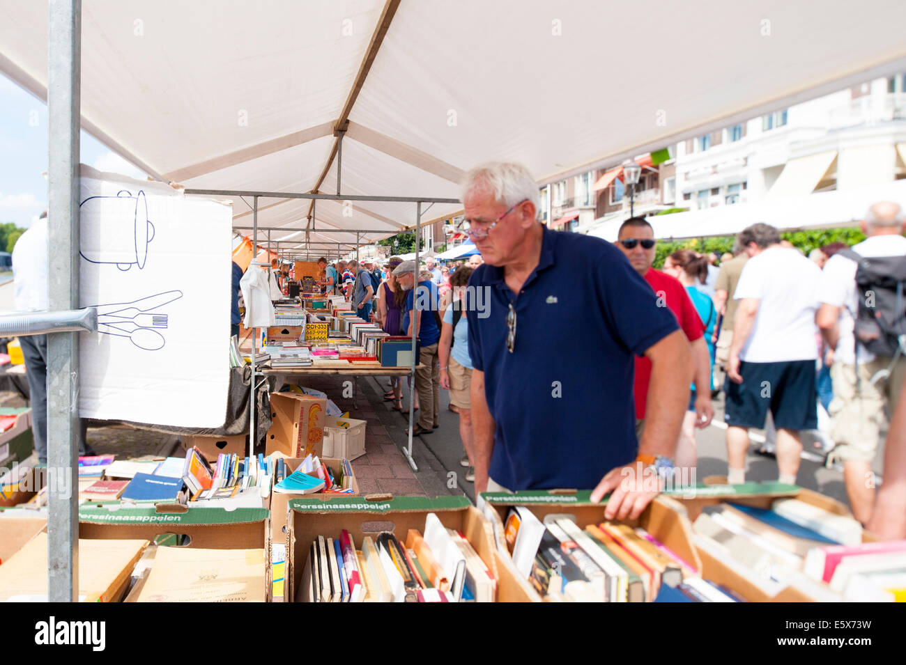 People shop at the Deventer book market in the Netherlands. Focal point is tilted and shifted at the row of books. - Stock Image