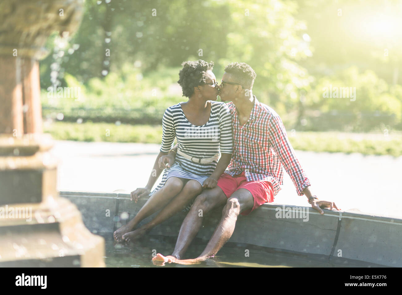 Young couple kissing with bare feet in Bethesda fountain, Central Park, New York City, USA - Stock Image