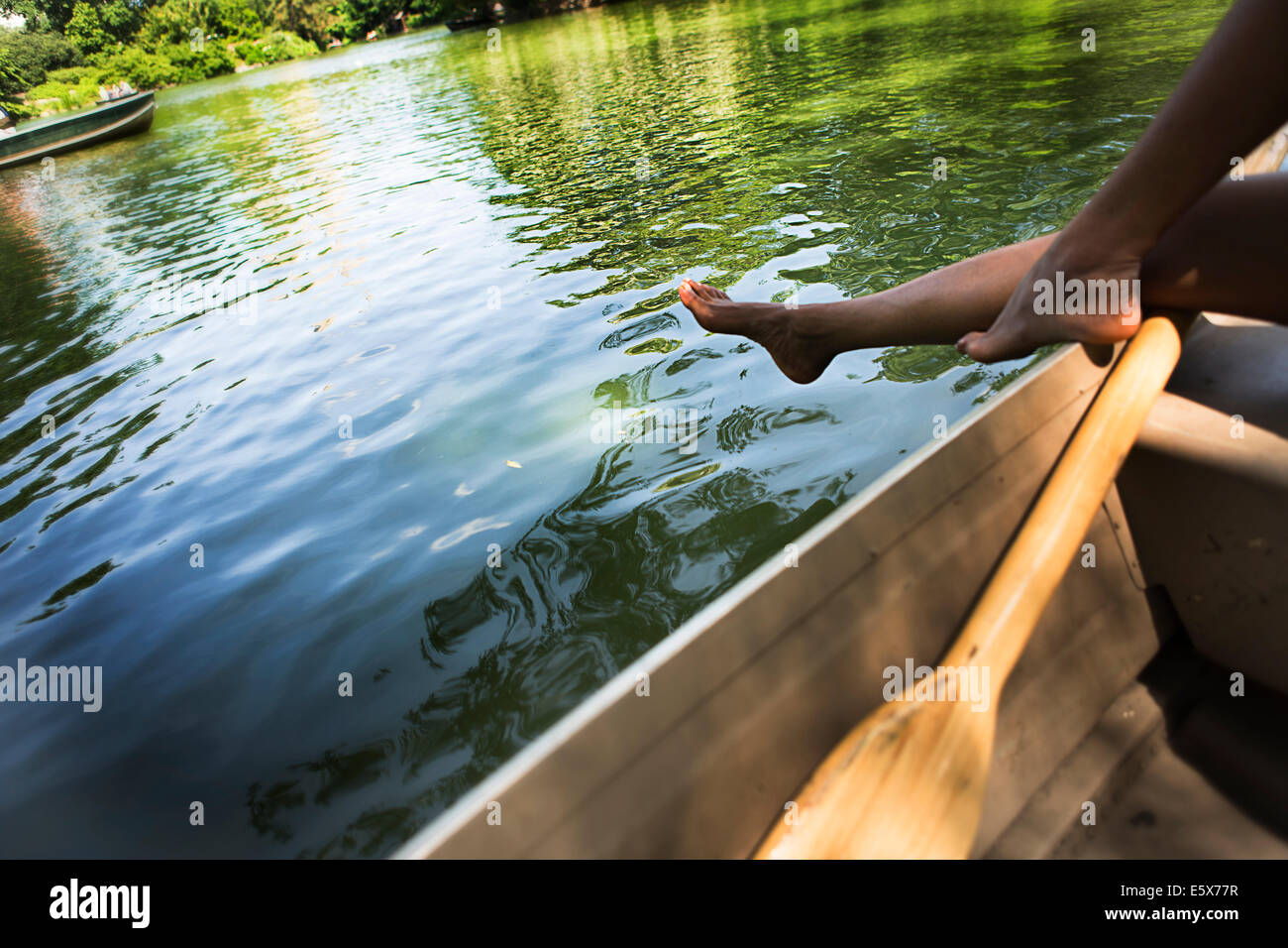 Cropped image of young woman's legs in rowing boat on lake in Central Park, New York City, USA - Stock Image