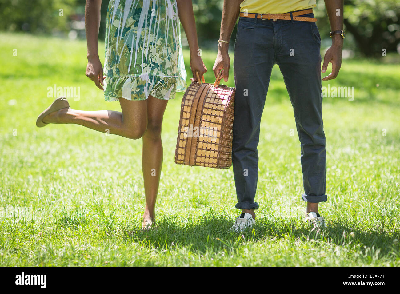 Cropped image of young couple with picnic basket in park - Stock Image
