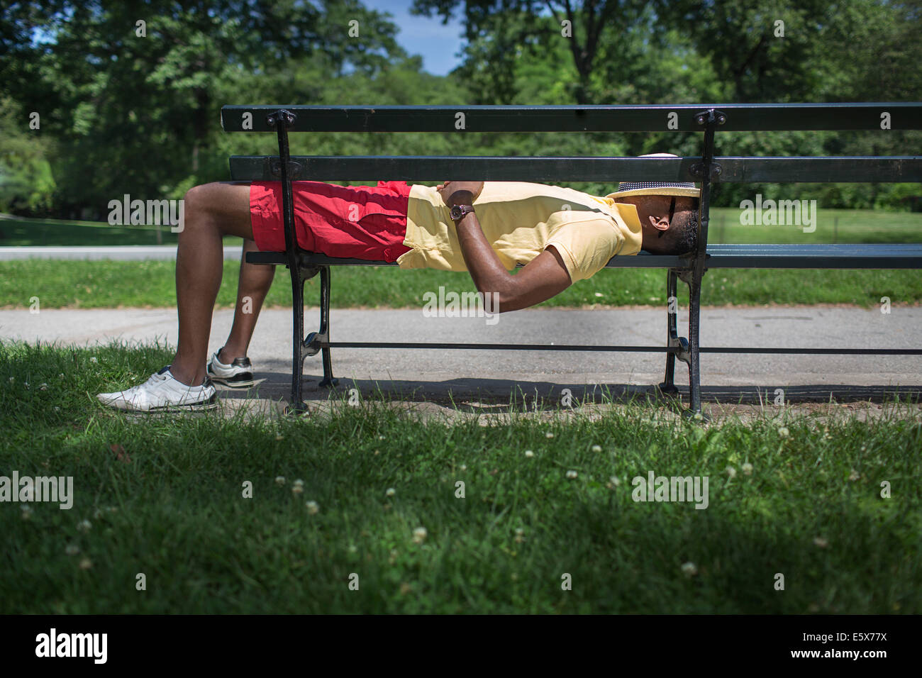 Side view of young man lying on park bench with fedora covering face - Stock Image