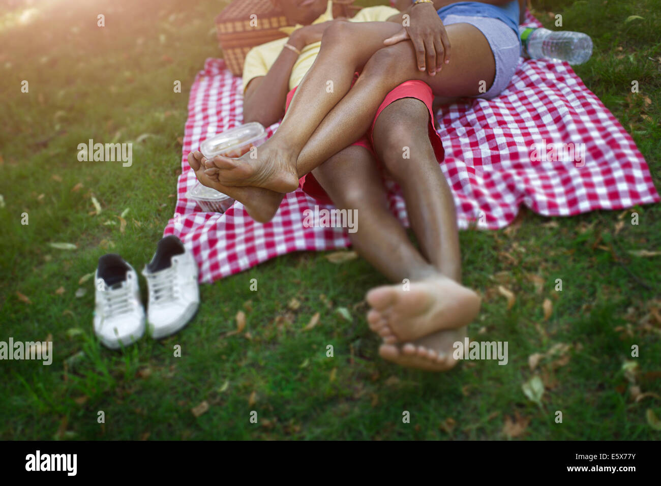 Cropped image of young couple in lying in park on picnic blanket - Stock Image